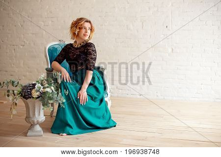 Image of elegant girl sitting in retro style armchair. Redhaired curly young beautiful model.