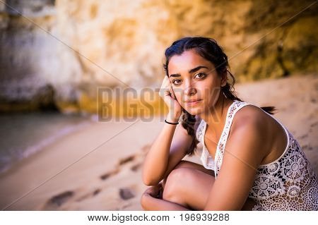 Potrait Latin Girl Sitting On Golden Sand At Beach Near Rocks And Looking At Ocean.  Summer Vocation