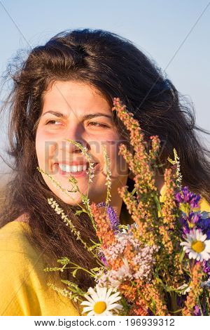 Cute young smiling girl portrait with field flowers during summer sunset