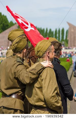BERLIN - MAY 09, 2015: Soldiers in the uniform of the Red Army during the war and with the flag of the Soviet Union.