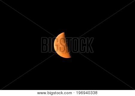 Photo of a young red moon against the background of a dark sky