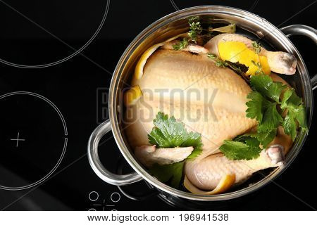 Cooking pot with turkey soaked in flavored brine on electric stove