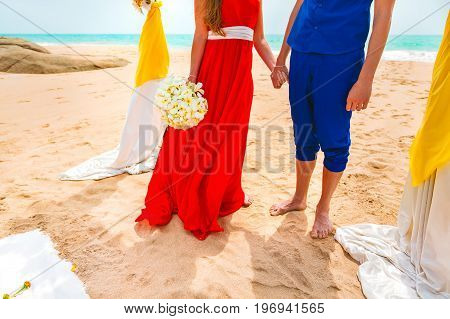 A picture of a happy couple holding hands at the beach. Relaxing at sunset during vacation. Newlyweds at the honeymoon. Wedding ceremony near the sea. Close-up