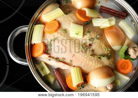 Cooking pot with turkey soaked in flavored brine on stove, closeup