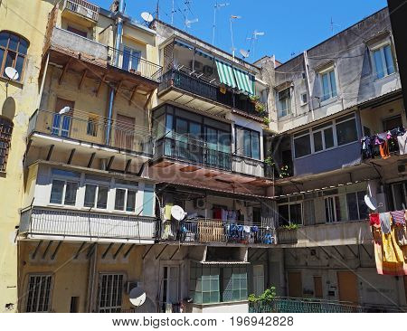 colourful inner yard in old Neapol apartment house with balcony flowers clothes and antens