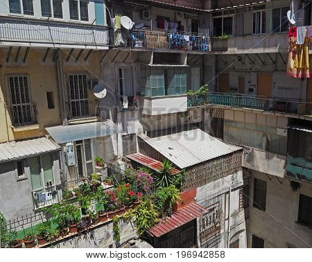 colorful inner yard in old Naples apartment house with balcony flowers clothes