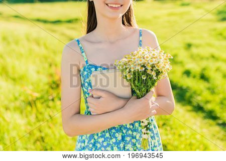 Young smilling romantic girl hugging book and bouquet of wildflowers on the background of juicy green grass