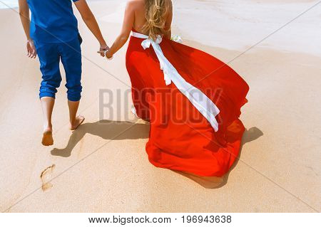 Back view of loving couple holding hands. Lovers walking away with footprints at a sandy beach