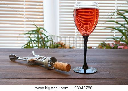 One Wineglass Of Red Pink Wine On Dark Desk