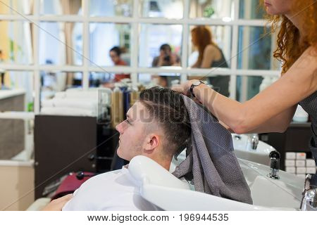 The Girl The Hairdresser Washes Her Hair After Cutting The Young, Handsome Guy In The Beauty Salon