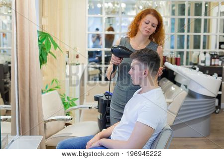 Male Client Getting Haircut. Girl Hairdresser Dries My Hair A Young, Attractive Guy In A Beauty Salo