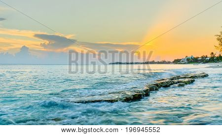 Flat rock sticking out of the Caribbean sea at sunset by Cemetery Beach, Grand Cayman