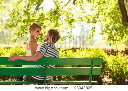 Romantic Couple Sitting On Bench In Park