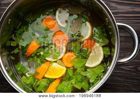 Cooking pot with flavored brine for turkey on wooden table