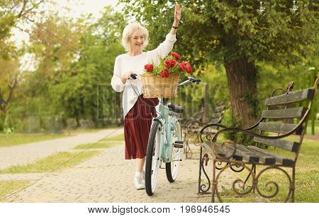 Beautiful middle aged woman waving her hand in park
