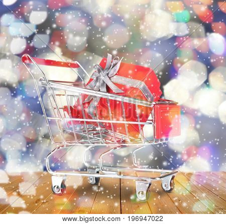 Shopping cart with gift on blurred lights background, snow effect. Boxing day concept