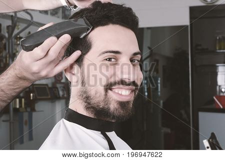 Close up of young man having a haircut with hair clippers.