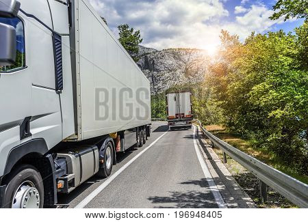 Two trucks on a narrow mountain road.