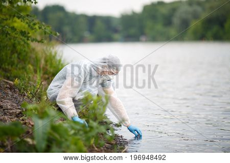 Ecologist takes sample of water