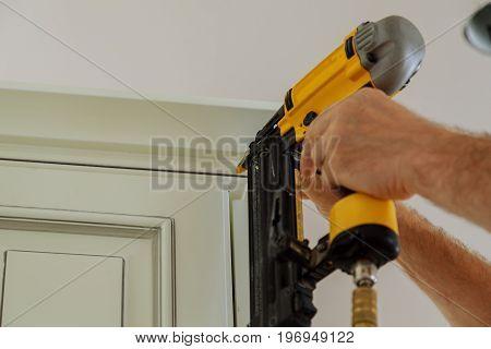 Carpenter Brad Using Nail Gun To Crown Moulding On Kitchen Cabinets Framing Trim,