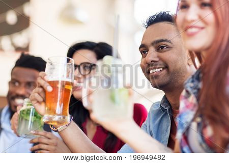party, holidays and people concept - group of happy international friends with drinks at restaurant