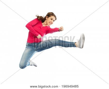 sport, martial arts, motion and people concept - smiling young woman jumping in air and fighting over white background