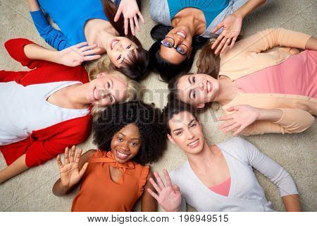 diversity, race, ethnicity, gesture and people concept - international group of happy smiling different women lying on floor in circle and waving hands