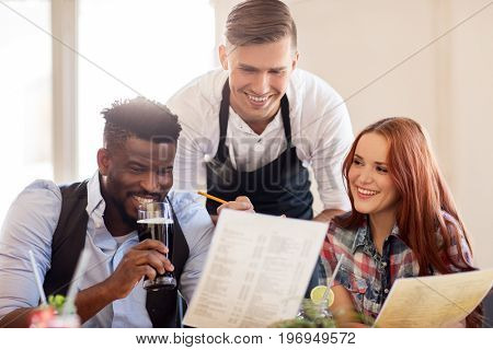 service and people concept - happy couple with menu and drinks and waiter with notepad receiving order at bar or restaurant