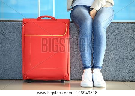 Girl legs in blue jeans near red suitcase close-up. Passenger traffic background