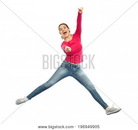 happiness, freedom, motion and people concept - smiling young woman jumping in air and pointing finger to you over white background