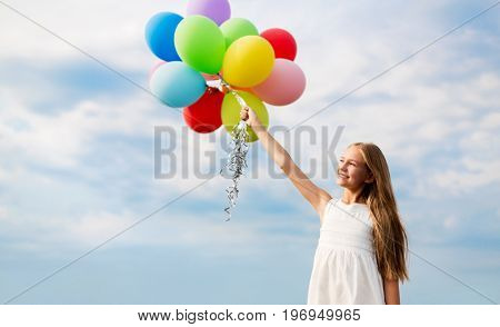 summer holidays, childhood and people concept - happy girl in sunglasses with air balloons outdoors