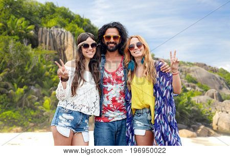 summer holidays, travel and people concept - smiling young hippie friends in sunglasses showing peace hand sign over tropical island beach background