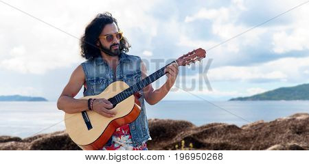 music, travel and people concept - young hippie man playing guitar and singing over sea background
