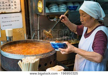 Tokyo Japan - August 30 2016: Japanese street food vendor preparing food on Tsukiji fish market in Tokyo