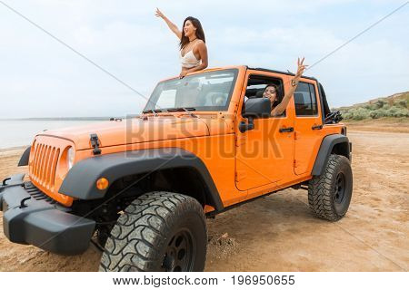 Two beautiful young women having fun while driving a car at the beach