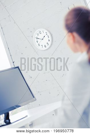 business, office, school and education concept - businesswoman looking at wall clock in office
