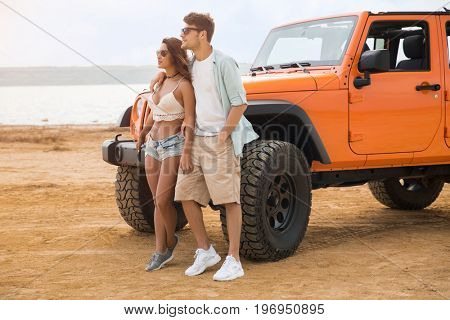 Beautiful young couple standing together near their car at the beach