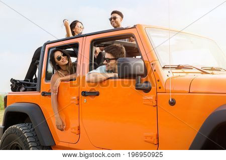 Group of happy young people laughing and having fun on a road trip