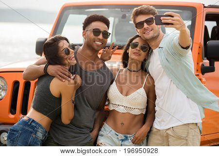Group of young cheerful friends talking a selfie together while standing outdoors with a car on a background