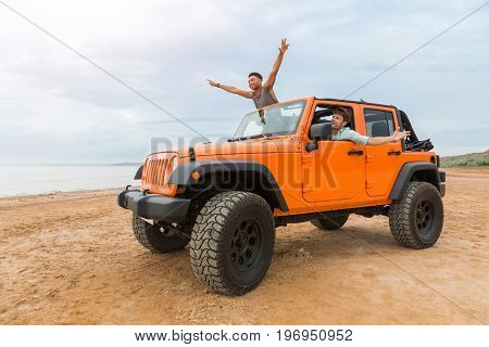 Two handsome young men having fun while driving a car at the beach