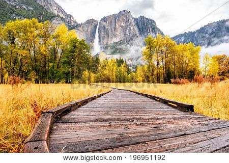 Meadow with boardwalk in Yosemite National Park Valley with Yosemite Falls at cloudy autumn morning. Low clouds lay in the valley. California, USA.