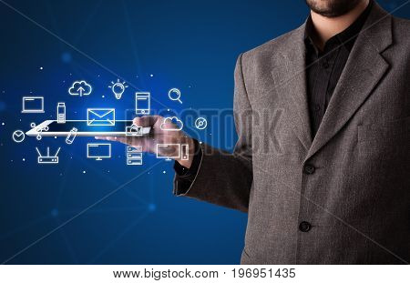 Casual businessman holding tablet with multimedia icons