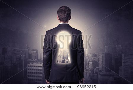 Young businessman standing and thinking with keyhole on his back and city graphic around