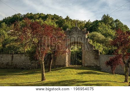 Bomarzo, Italy - May 20, 2013. View of stone wall and gate at sunset amidst the vegetation in the Park of Bomarzo, also known as Park of Monsters, near Viterbo. Located in the Lazio region, central Italy