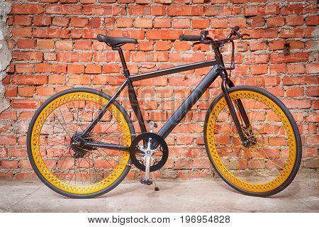 Black simple electric bike against brick wall