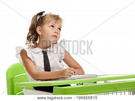 Young pretty schoolgirl sitting at the desk and dreaming during lesson