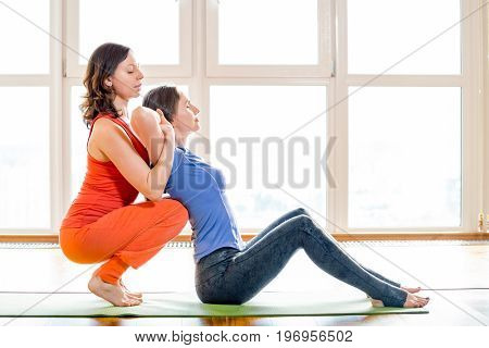 Two beautiful woman in bright colorful sportswear making yoga exercises sitting on mat at yoga studio. Indoor shot. Thai massage element. Treatment, rest, relaxation. Big windows in the background