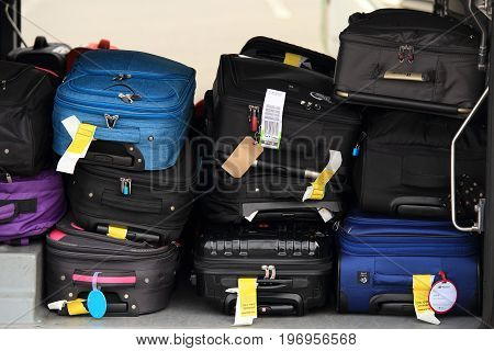 Copenhagen airport, Denmark - July 15, 2017: Passenger luggage in airplane. Colorful suitcases in airplane close-up.