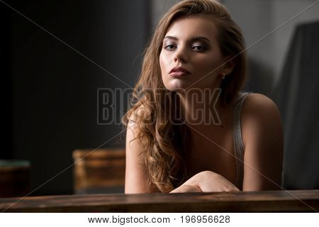 Beautiful brunette wearing sexy beige dress relaxing on wooden sofa studio shot