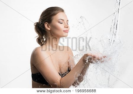 Young beautiful woman her eyes shut catching water stream and splashes falling in her hands from above studio portrait